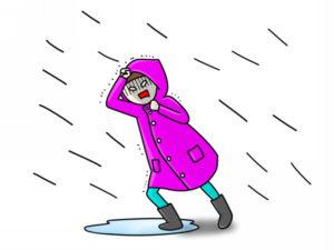 台風で雨に打たれる人