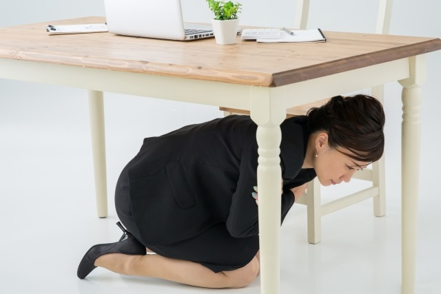 机の下に避難する人